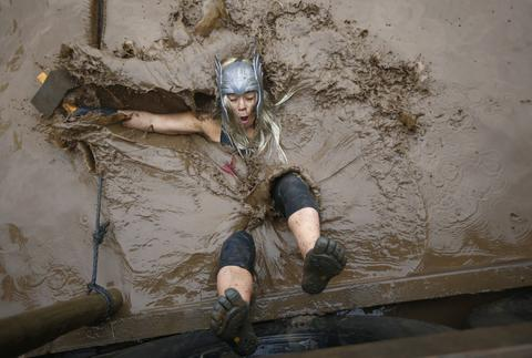 A competitor falls in to muddy water during the Tough Guy event in Perton, central England, January 26, 2014. The annual event to raise cash for charity challenges thousands of international competitors in a cross country run followed by an assault course consisting of obstacles including water, fire and tunnels.