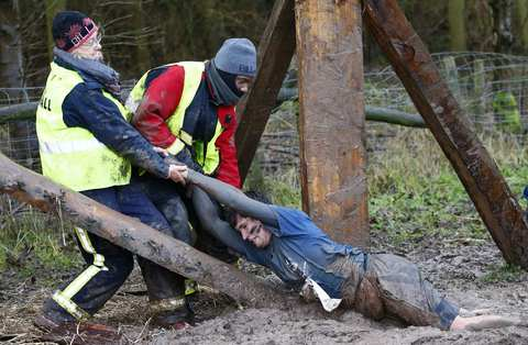 A competitor is dragged out of the mud during the Tough Guy event in Perton, central England, January 26, 2014. The annual event to raise cash for charity challenges thousands of international competitors in a cross country run followed by an assault course consisting of obstacles including water, fire and tunnels.