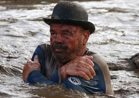 A competitor wades through muddy water during the Tough Guy event in Perton, central England, January 26, 2014. The annual event to raise cash for charity challenges thousands of international competitors in a cross country run followed by an assault course consisting of obstacles including water, fire and tunnels.