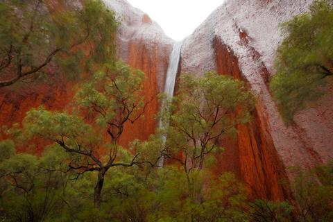 A waterfall is seen in Kantju Gorge as it rains at Uluru on November 27, 2013 in Uluru-Kata Tjuta National Park, Australia. Uluru/ Ayers Rock is a large sandstone formation situated in central Australia approximately 335km from Alice Springs. The site and its surrounding area is scared to the Anangu people, the Indigenous people of this area and is visited by over 250,000 people each year.