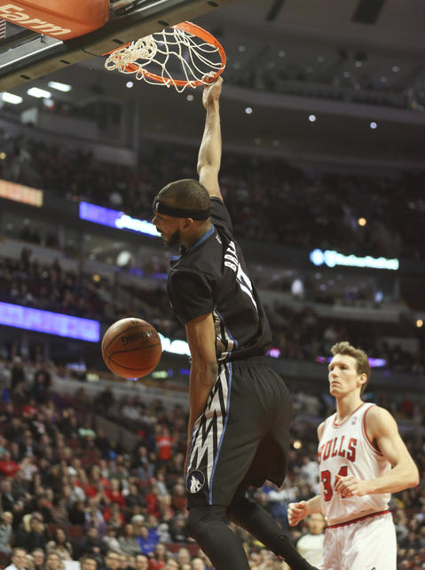 The Timberwolves' Corey Brewer hangs on the rim after a dunk on a breakaway in front of Mike Dunleavy during the second half.