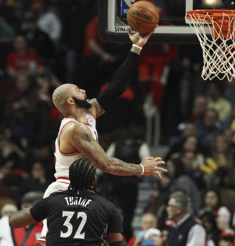 Carlos Boozer goes to the basket in front of the Timberwolves' Ronny Turiaf during the second half.