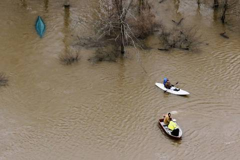 Boaters pass an overturned canoe in the flooded Des Plaines River near Wheeling.