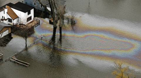 An aerial view shows an apparent oil or gas leak from flooded homes along the Fox River near Island Lake.