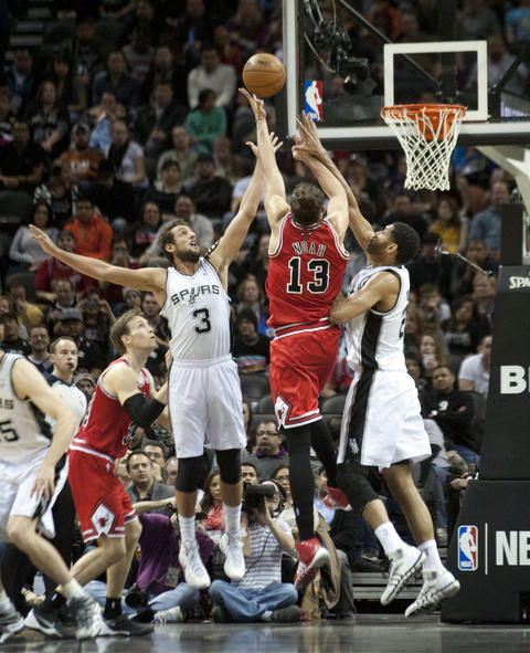 Joakim Noah shoots against the Spurs' Tim Duncan and Marco Belinelli during the first half.