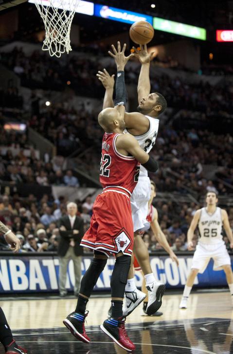 The Spurs' Boris Diaw shoots against Taj Gibson during the first half.