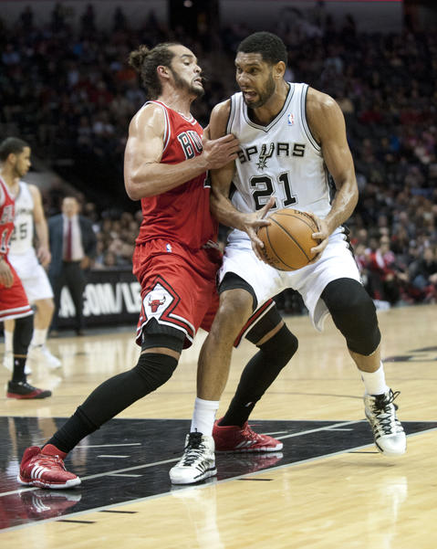The Spurs' Tim Duncan drives against Joakim Noah during the first half.