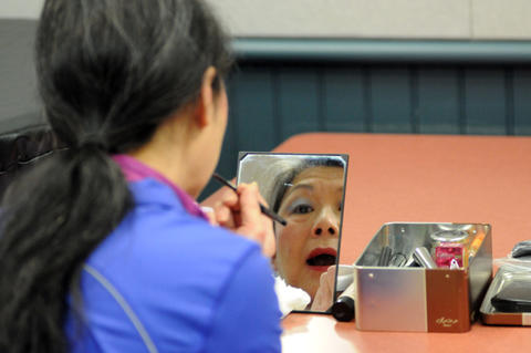 Julie Lai of the Asian Performing Arts group puts on makeup before rehearsed for their performance at the Enfield Heritage Fair at the Welles Turner Glastonbury Memorial Library in Glastonbury Wednesday Jan. 29.