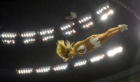 A Ravens cheerleader soars through the air at the Superdome.