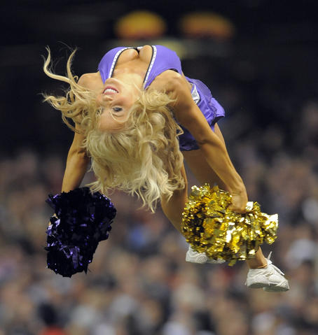A Ravens' chearleader is thrown into the air.