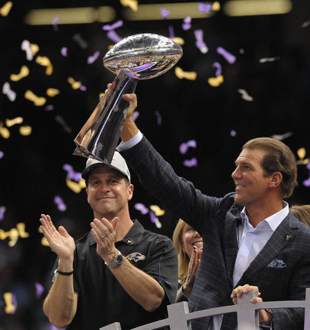 Owner Steve Bisciotti holds the Lombardi Trophy as coach John Harbaugh applauds behind him.