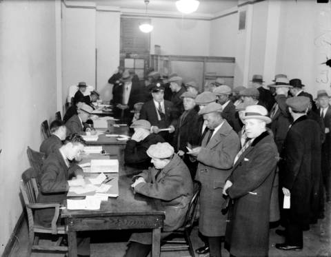 "Veterans fill out applications for bonus loans inside the new branch of the Veteran's Bureau at 206 W Van Buren Street on March 2, 1931. The Tribune reported that more than $100,000 was paid out in loans to veterans during that day. When the Tribune asked John Karela, who was waiting in line, what he was going to do with the money, he replied, ""That's a silly question. I'm going to buy my five kids -the youngest is 18 months, the oldest is 9 years-old- some good solid food. I'm going to buy 'em shoes."""