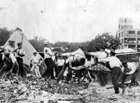 Veterans throw bricks and stones at charging policemen as the police try to evict the Bonus Army from camping on government property on July 28, 1932. One of the rioters is seen swinging a section of pipe. The fight was one of several clashes in Washington in which several lives were lost before the United States Army was called to oust the marchers. The veterans demanded immediate payment of their bonuses by the government, and lost.