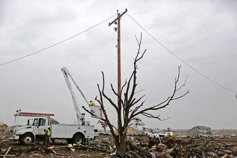 Crews work to restore electricity in the areas hit by the tornado that tore through Washington, Ill. on Nov. 17.