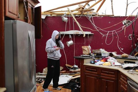 Emily Heuermann, 19, uses her phone to document the damage to the family home of her friend Maura O'Brien.