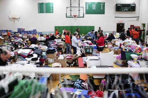 Volunteers and and people in need sort though donated goods and clothing in the wake of Washington, Ill. tornado, at Saint Patrick Catholic School. School and church officials converted the gymnasium into a disaster relief center following the storm.