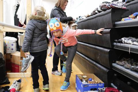 Emily Bandy, 8, whose family home was destroyed by last week's tornado, tries on a new pair of shoes at Saint Patrick Catholic School in Washington, Ill. School and church officials converted the gymnasium into a disaster relief center following the storm.