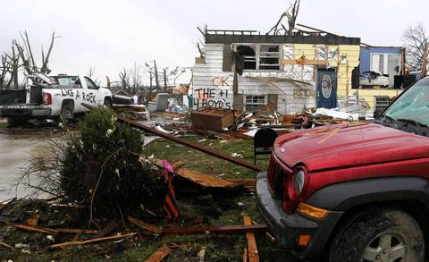 Messages spray-painted on a damaged truck and home are visible as members of the Illinois Emergency Management Agency assess the conditions of homes in the areas hit by the tornado in Washington, Ill.