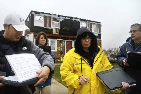 Members of the Illinois Emergency Management Agency assess the conditions of homes in the areas hit by the tornado in Washington, Ill.