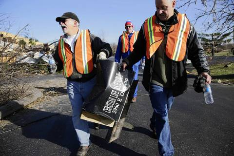 Volunteers Steve Russell, left, and Ted Soltys, right, return a mailbox to Christian Life Assembly church in Diamond, Ill.