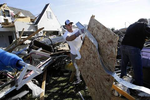 Chicago Bears' player Tom Zbikowski helps load debris into a dump truck in the Diamond Ridge neighborhood in Coal City, Ill.