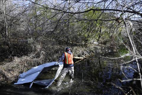 Volunteer Bradley Graham cleans debris from a stream behind Christian Life Assembly church in Diamond, Ill.
