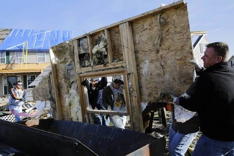 Residents and volunteers load debris into a dumpster in the Diamond Ridge neighborhood in Coal City, Ill.