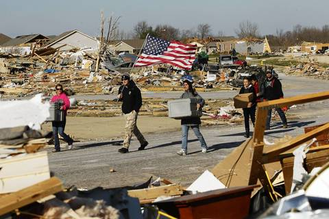 Jake Coyle of East Peoria, carries a flag with volunteers arriving to help friends dig out in the wake of a devastating tornado that struck Washington.