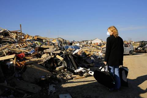 Jean Vires, 51, carries bags of rescued belongings as she helps her mother search in the wreckage of her destroyed home in Washington.