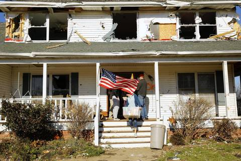Dan Learned's family removes items from his damaged home in Washington.