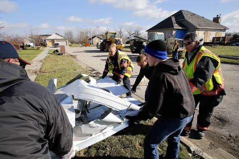 Coal City fire fighters help haul away a garage door in the Diamond Estates subdivision of Diamond, Ill., the day after a devastating tornado tore through the area.