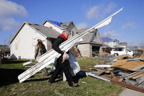 Doug Bentson, of Morris, Ill., helps residents of Diamond Estates subdivision in Diamond, Ill., the day after a devastating tornado tore through the area.