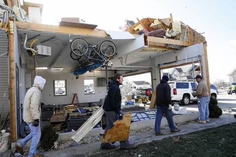 Residents pass by damage caused by a severe tornado that hit the Diamond Estates subdivision in Diamond, Ill., the day before. The second floor and the garage wall wer torn away on this house on Laura Lane.