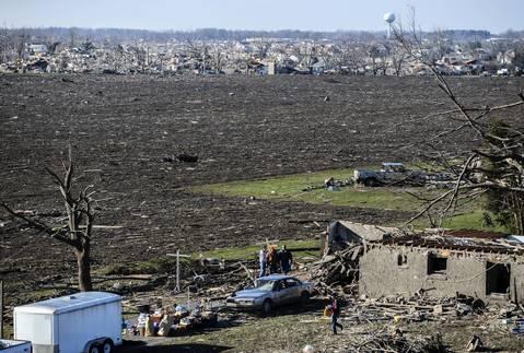 People look over tornado damage in Washington, Ill.