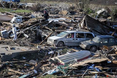 Two people look through the debris in Washington, Ill.
