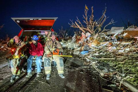 Firemen rest after searching through the remains of homes along Devonshire Road in Washington, Ill., after a tornado tore through the area.