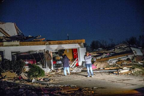 People stare at the remains of homes along Devonshire Road in Washington, Ill. Sunday night. A tornado tore through the area earlier in the day, destroying a number of homes.