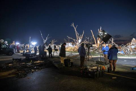 Members of the media prepare for morning newscasts in Washington, Ill., the morning after a devastating tornado tore through the area.