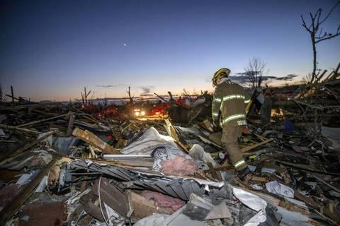 A fireman searches through devastation along Devonshire Road in Washington, Illinois.