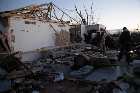 Residents survey damage to their home along Devonshire Road in Washington, Ill., after a tornado tore through the area.