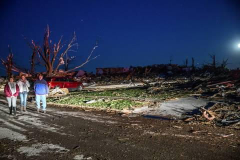 Families return to search for belongings along Devonshire Road in Washington, Ill., after a tornado tore though the area.
