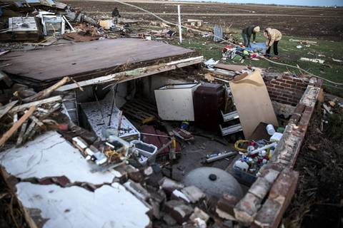 Ben Dubois and his father Mark look over the remains of Ben's home on Main Street in Washington, Ill., after a tornado tore through the area earlier in the day.