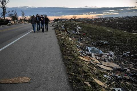 People walk along North Main Street in Washington, Ill., hours after a tornado tore through the area.