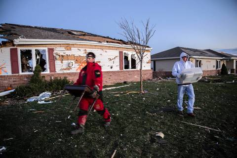 Residents carry items from their damaged homes along Devonshire Road in Washington, Ill., after a tornado tore through the neighborhood.