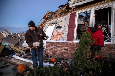 Dan Elbert, left, helps his friends on Devonshire Road in Washington, Ill., after a tornado swept through the neighborhood, destroying many homes.