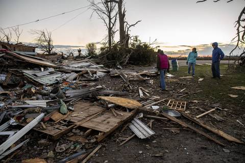 Lindsay Dubois, left, surveys the remains of her home on North Main Street in Washington, Ill., after a tornado tore through the area destroying a number of homes.