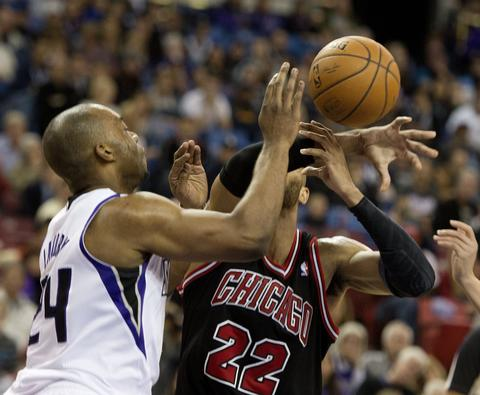 The Kings' Carl Landry blocks the shot attempt by Taj Gibson in the first quarter.