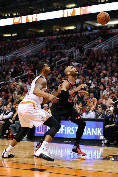 Taj Gibson yells as the ball goes in the air while being defended by the Suns' Markieff Morris in the first half.