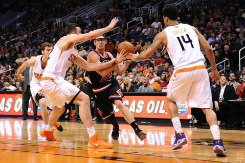 Kirk Hinrich drives the ball against the Suns' Miles Plumlee and Gerald Green in the first half at US Airways Center.