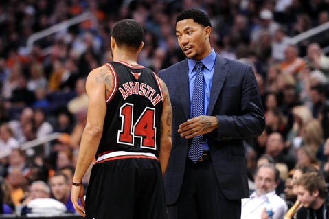 Derrick Rose talks with D.J. Augustin during a timeout against the Suns.